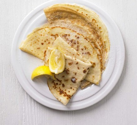 Pancakes on a plate with lemon wedges