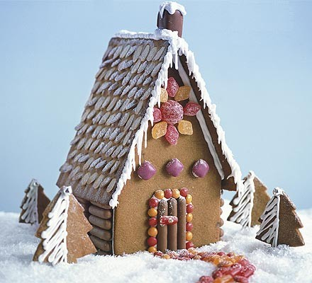 A tall gingerbread house in a snowy Christmas scene