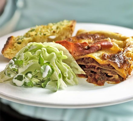 Classic lasagne on a plate with salad