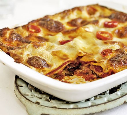 Roasted vegetable lasagne in a dish with portion out