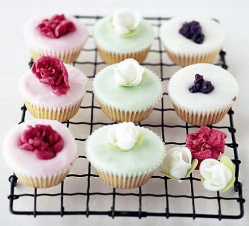 Eight fairy cakes with different colour icing and rose decorations