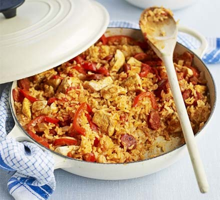 Chicken & chorizo jambalaya in a shallow cast iron dish with wooden spoon
