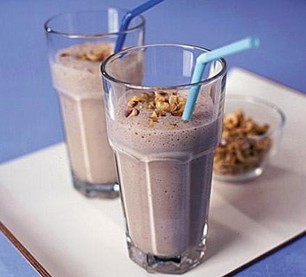 Glass of banana, honey & hazelnut smoothie with straw