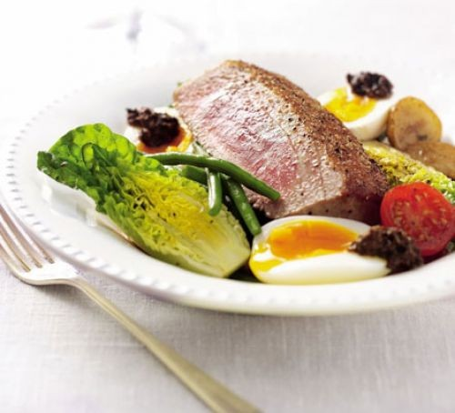 Salad niçoise in a bowl with a tuna steak on top