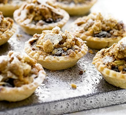 Several mince pies topped with pastry star and crumble