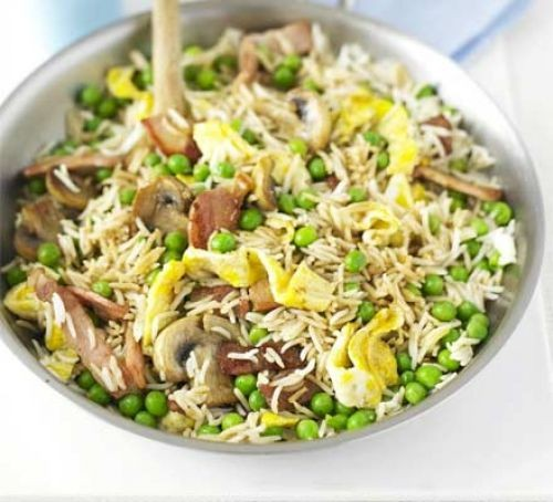 Fried rice with bacon, mushrooms and peas in pan with spoon
