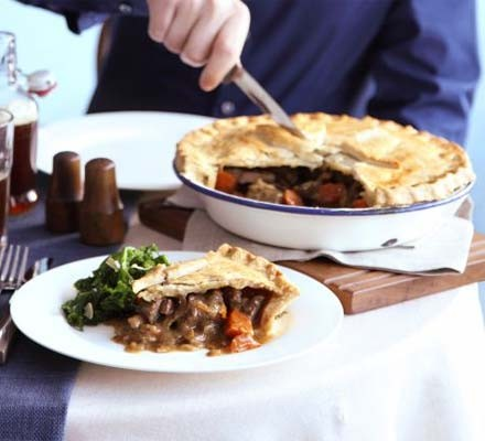 Beef, ale & mushroom pie in a round pie dish with slice out on a plate