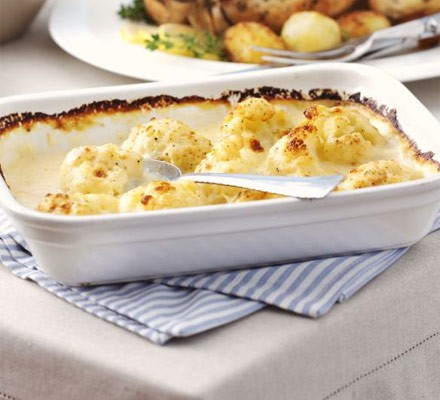 Cauliflower cheese in large dish with spoon