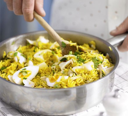 Kedgeree in a deep saucepan with wooden spoon