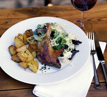 Confit of duck on a plate with roast potatoes