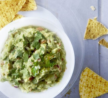 Chunky guacamole in a bowl with tortilla chips