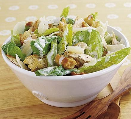 Chicken Caesar salad in a bowl with wooden salad servers