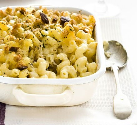 Close up of macaroni cheese in a serving dish with a serving spoon alongside