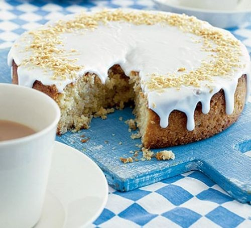 Cake topped with white coconut drizzle icing and shavings