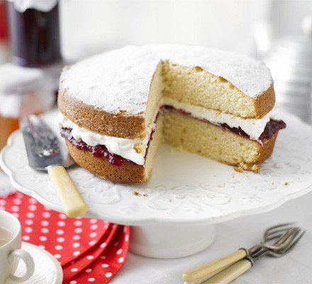 Victoria sponge on a cake stand with slice taken out