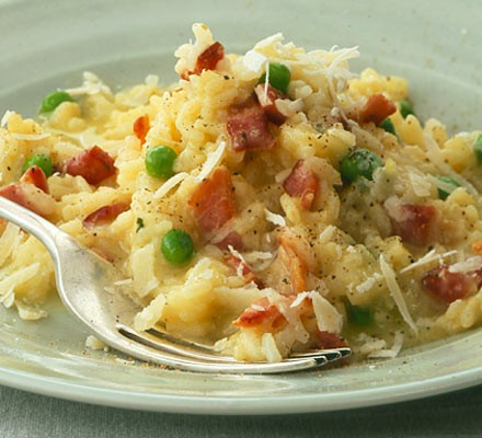 Serving of risotto with bacon & peas with fork