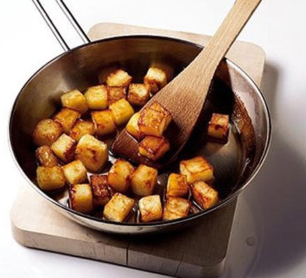 Perfect sautéed potatoes in frying pan with wooden spatula