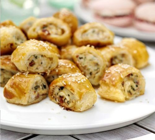 Sausage rolls piled on a plate