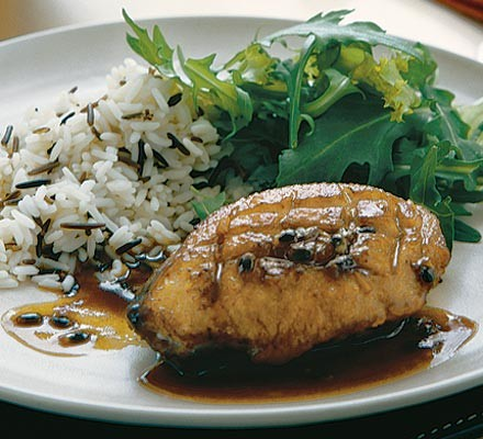 Duck breast in sauce, with rice and salad on a plate