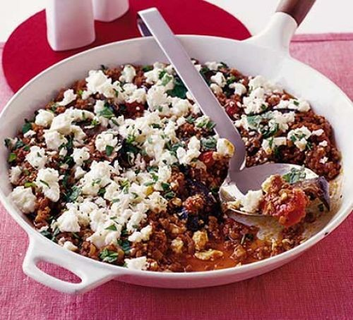 Moussaka topped with feta cheese in a round dish