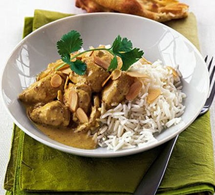 Light chicken korma in a bowl with flaked almonds, herbs and rice