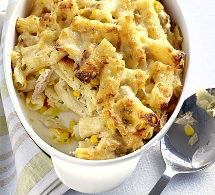 Tuna pasta bake in an oval baking dish with portion out