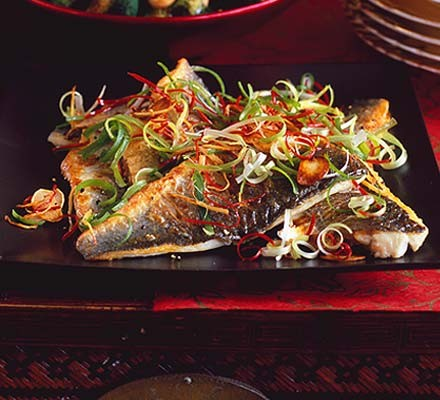 Sea bass fillets with sizzled ginger, chilli & spring onions on a black plate