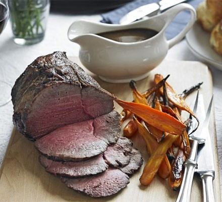 Roast beef & carrots on a chopping board with gravy boat