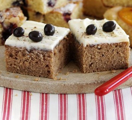 Two squares of cappuccino cake topped with frosting and coffee beans