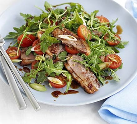Duck salad on a plate with lettuce, tomatoes and soy dressing