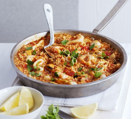 Paella in a large pan with serving spoon and lemon wedges