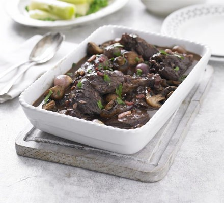 Coq au vin in a rectangular serving dish with spoon