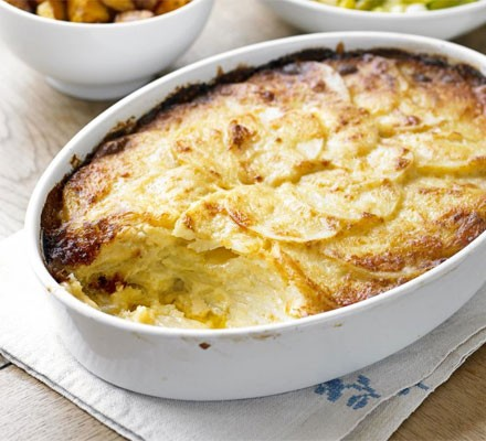 Dauphinoise potatoes in an oval dish with portion out