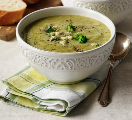 Broccoli and stilton soup in a patterned bowl with napkin & spoon