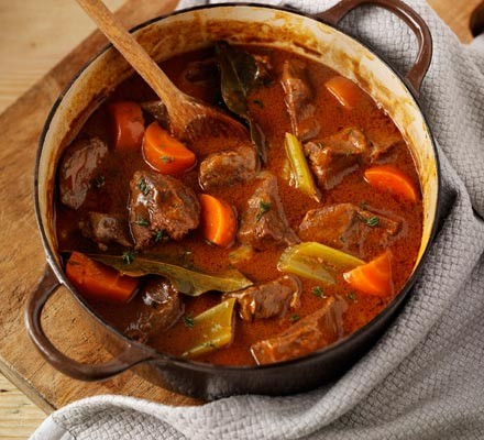 Beef & vegetable casserole in a cast iron pot with wooden spoon