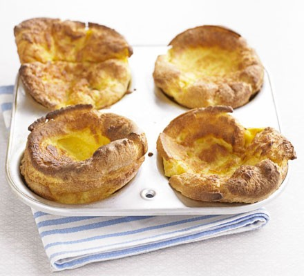 Four Yorkshire puddings in a baking tin