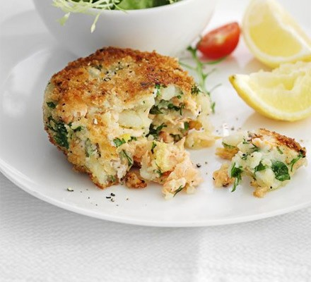 Salmon fish cake on a plate with lemon wedges and salad
