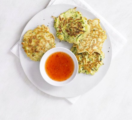 Courgette fritters on a plate with bowl of sweet chilli sauce
