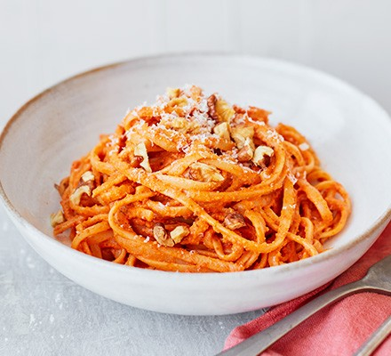 Red pepper linguine served in a bowl and garnished with parmesan