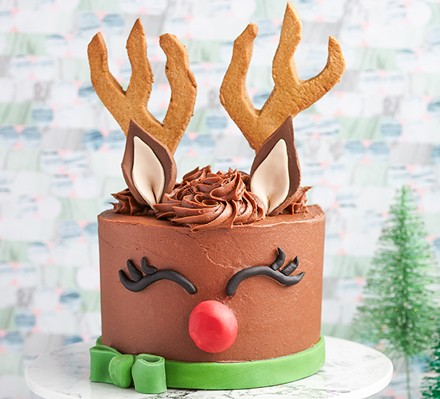 Reindeer cake with antlers and red nose on cake stand with Christmas tree