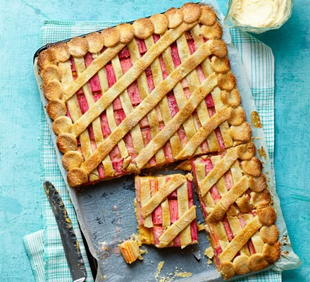 Rhubarb and custard pie with a lattice top on a blue board