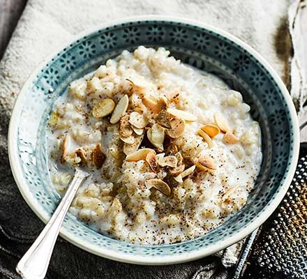 A bowl of slow cooker rice pudding with almonds flaked on top