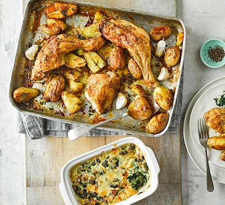 Roast chicken with squashed new potatoes & cheesy creamed spinach in a roasting dish