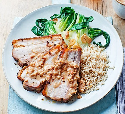 A plate serving roast pork belly with caramelised peanut sauce