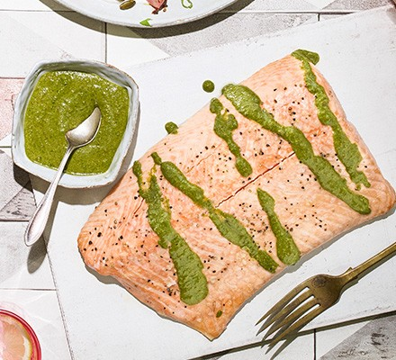 Roasted salmon with a small dish of chermoula on the side