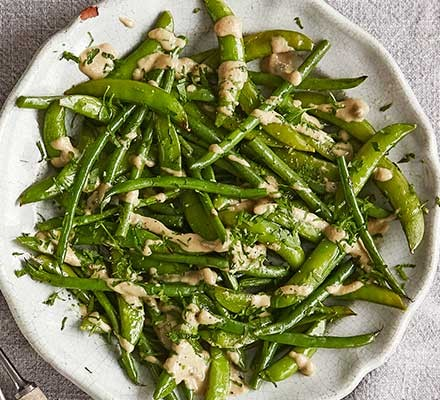Roast sugar snaps & green beans with tonnato dressing served on a plate