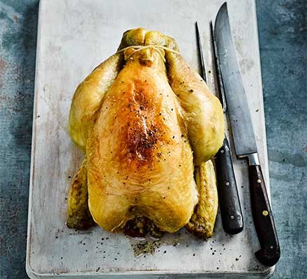 A whole cooked chicken with browned skin on a chopping board