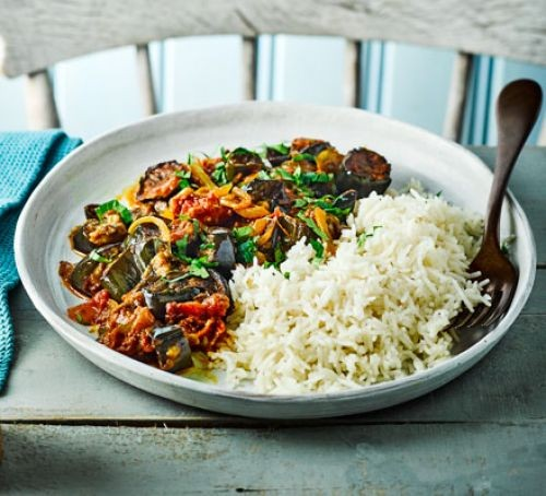 Aubergine, tomato and spinach curry with rice on a plate