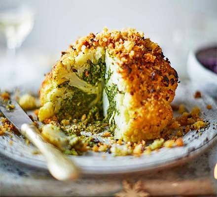 A roasted stuffed cauliflower on a plate