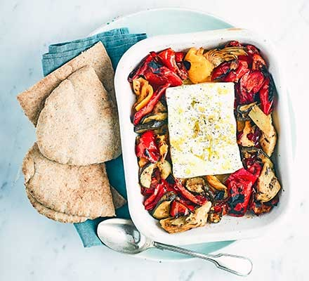 A casserole dish serving roasted feta and grilled vegetables